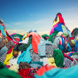 Big heap of colorful clothes on sky background...