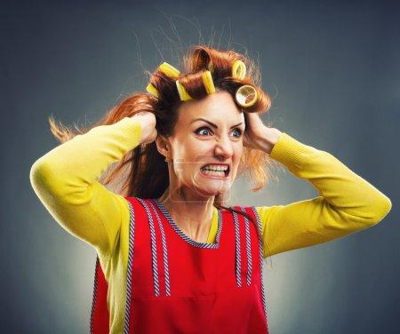 Photo pour Femme au foyer folle avec des bigoudis isolés sur gris - image libre de droit