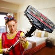 Portrait of housewife with vacuum cleaner cleaning...
