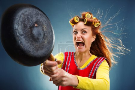 Photo for Crazy housewife with pan and curlers on her head - Royalty Free Image