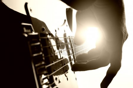 Photo for Guitarist plays on stage. Closeup view - Royalty Free Image