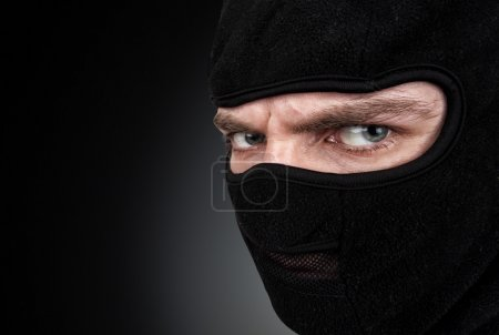 Portrait of man in a mask on black background...