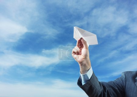Businessman holding paper plane in his hand