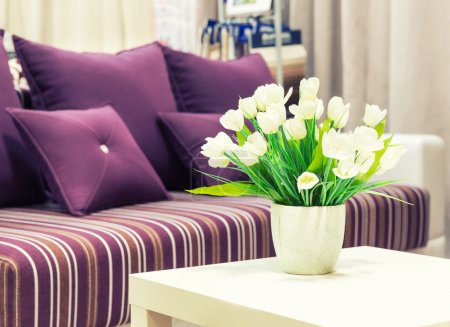 Photo for Flowers in a vase against sofa with velvet pillows - Royalty Free Image