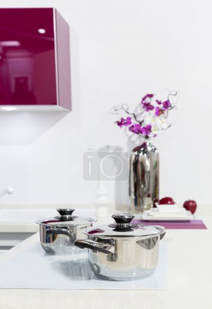 Photo for Nice white kitchen interior with orchid flower and saucepan - Royalty Free Image