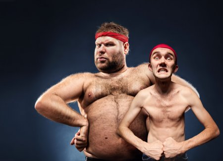 Photo for Funny fat and thin body builders show their muscles - Royalty Free Image