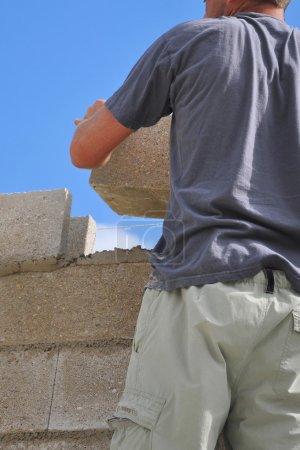 Photo pour Maçon mettant en place un mur de bloc de cendres - image libre de droit