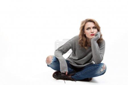 belle femme blonde assise sur le plancher
