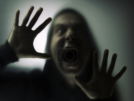 Photo for Angry man in a hood behind the glass - Royalty Free Image