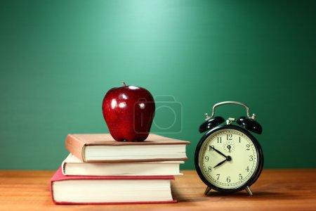 Photo pour Retour aux livres scolaires, apple et horloge sur le Bureau - image libre de droit