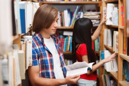Photo for Students in a library choosing a book - Royalty Free Image