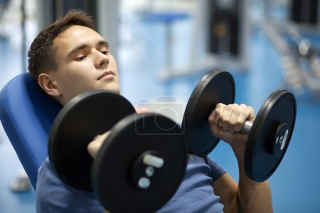 Photo for Handsome man with dumbbells in a gym - Royalty Free Image