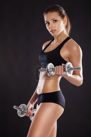 Photo for Sporty woman with dumbbells studio photo - Royalty Free Image