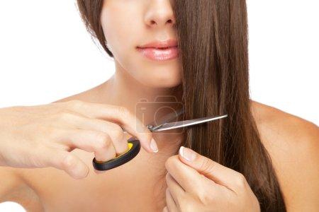 Beautiful young woman cutting her hair