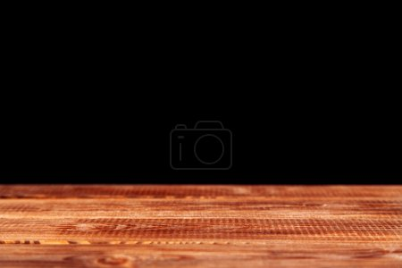 Wooden table on black background