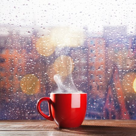 Photo for Steaming cup of coffee over a cityscape background - Royalty Free Image