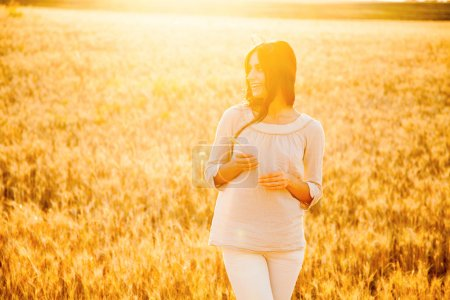 Photo for Beautiful brunette lady in wheat field at sunset - Royalty Free Image