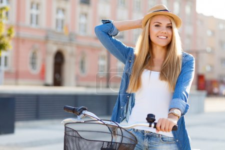 Photo for Young stylish woman with a bicycle in a city street - Royalty Free Image