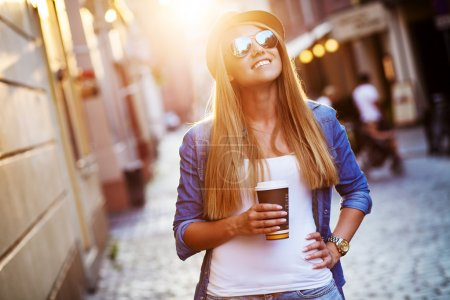 Photo for Young stylish woman drinking coffee to go in a city street - Royalty Free Image