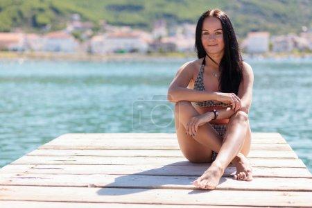 junge schöne Frau sitzt an einem Pier