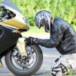 Man on his knees near a sports bike on the road...