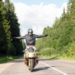 Sport bike rider with arms outstretched on the roa...
