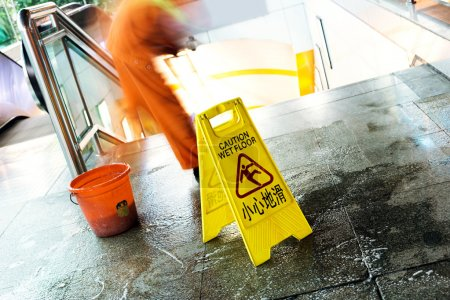 Photo for Cleaning in progress, and wet floor caution sign besides. - Royalty Free Image