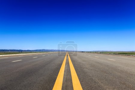 Highway in steppe against a blue sky
