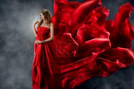 Photo pour Belle femme en robe de soie ondulée rouge comme une flamme. Regarder vers le bas . - image libre de droit