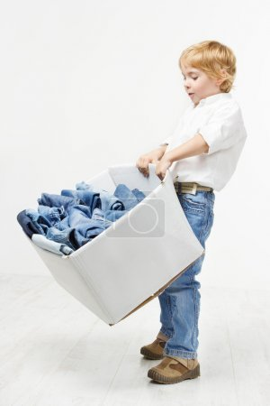 Child carrying cardboard box packed with jeans. Kids clothing fa