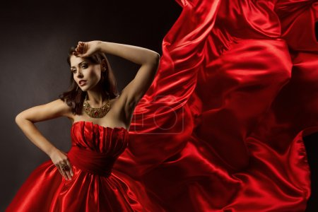 Photo pour Woman in red dress dancing with flying fabric, Fashion Model Girl Posing with waving cloth - image libre de droit
