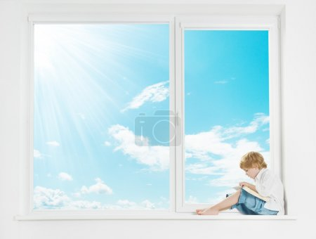 Window sunshine sky. Child on windowsill reading book.