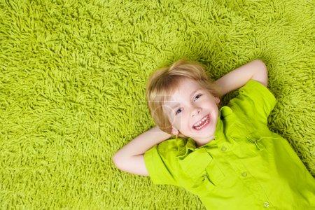 Photo pour Joyeux enfant couché sur le fond de tapis vert. Garçon souriant et regardant caméra - image libre de droit