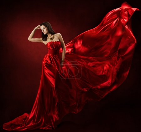 Photo pour Woman in red waving dress dancing with flying fabric - image libre de droit