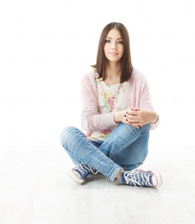 Photo for Beautiful girl teenager sitting on floor. White background - Royalty Free Image