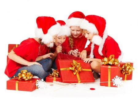 Foto de Ayudantes de Navidad para niños en caja de regalo de santa sombrero apertura presenta rojo. regalos de año nuevo - Imagen libre de derechos
