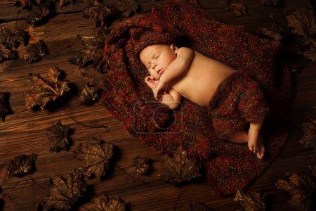 Photo for Baby newborn artistic portrait, kid sleeping in woolen hat on brown autumn fallen leaves - Royalty Free Image