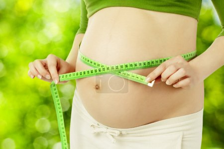 Pregnant belly, woman measure stomach. Prenatal health care concept