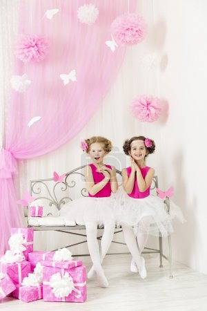Birthday party happy kids with presents. Girl sisters surprise by pink gift boxes
