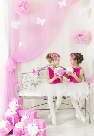 Girl giving children birthday present to sister. Kids and party gift boxes in pink color