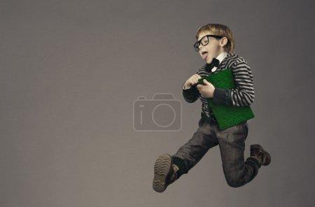 Photo pour Enfant porteur de ballon à l'école, portrait enfant drôle, sautant écolier intelligent avec des lunettes et livre - image libre de droit