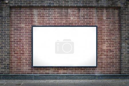 Photo pour Un panneau d'affichage blanc attaché à un mur de brique extérieur de bâtiments. - image libre de droit