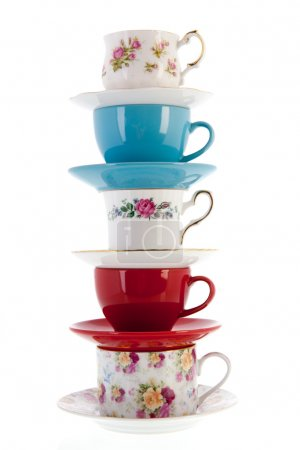 Stacked vintage coffee or tea cups isolated over w...
