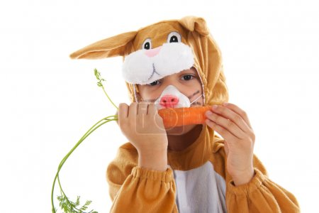 Photo for Child dressed as easter hare with carrots isolated over white background - Royalty Free Image
