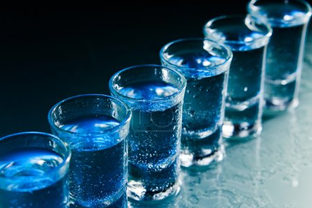 Photo for Glasses with an alcoholic drink on a damp glass table - Royalty Free Image