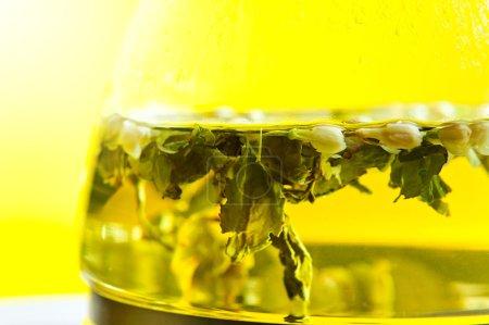 Photo pour Thé vert avec des fleurs de jasmin dans une théière en verre - image libre de droit