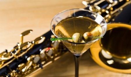 Photo for Saxophone and martini with green olives on wooden table - Royalty Free Image