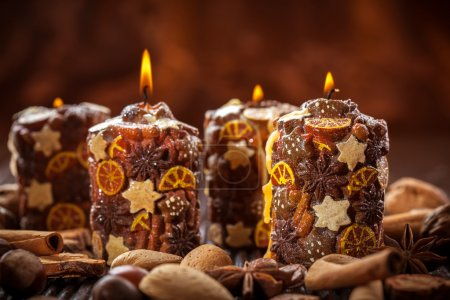 Photo for Rustic aromatic Christmas candles with spices and nuts - Royalty Free Image