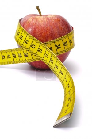 Photo for Apple with measure tape as symbol for diet and weight control - Royalty Free Image