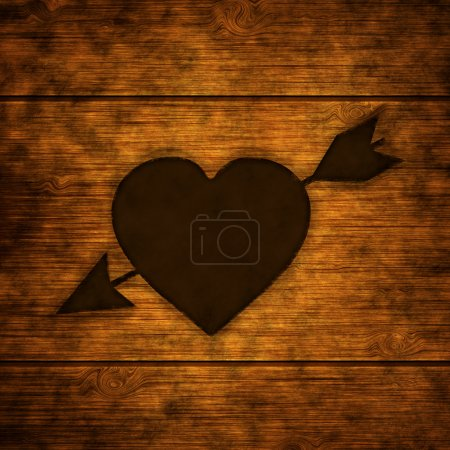 Wooden background with burnt heart